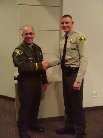 Sheriff Obenberger congratulating Deputy Hoskin